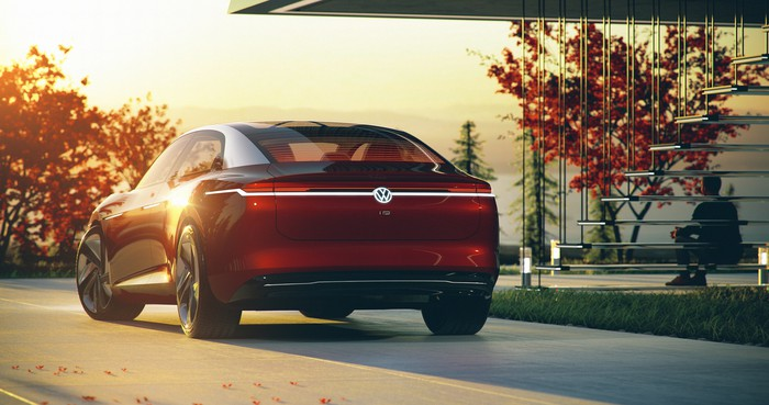 The VW I.D. Vizzion concept car is shown parked outside, photographed from behind.