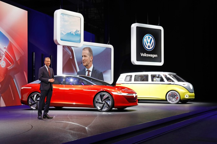 Diess is speaking on stage next to the I.D. Vizzion, a sleek red sedan, and the I.D. Buzz, a yellow and white minivan that recalls the styling of the 1960s VW Microbus.