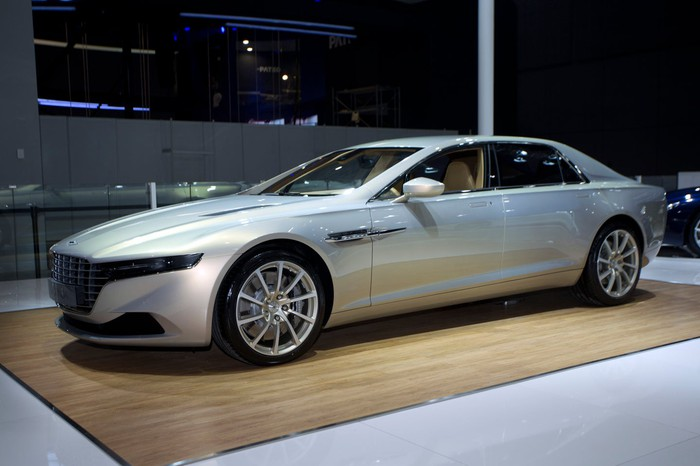 A 2015 Lagonda Taraf, a sleek luxury sedan, in silver on an auto-show display stand.