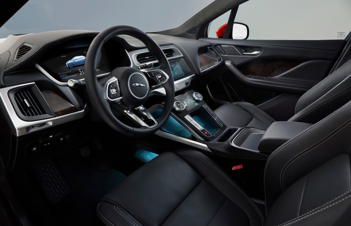 A view of an I-Pace's front seats and dashboard, showing black leather, dark wood, and brushed-metal trim.