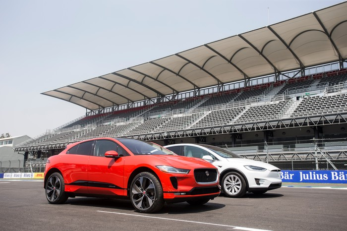 A red Jaguar I-Pace and a white Tesla Model X SUV, side-by-side on a race track.