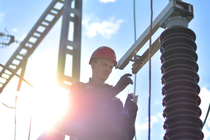 A man in a hard hat standing in front of electrical transmission equipment