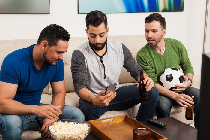 Three men watching TV and checking scores on a smartphone. One is eating popcorn, one is holding a soccer ball, and one is holding the phone.