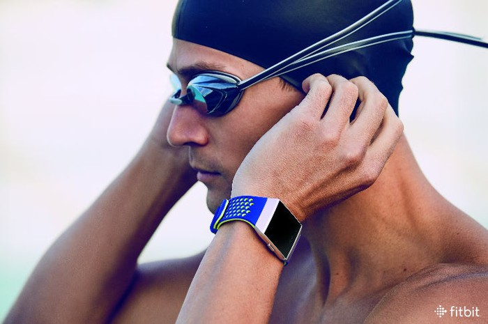 Man wearing swim cap, goggles, and Fitbit Ionic