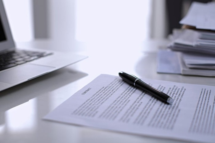 A laptop, pen, and paper contract sitting on a desk.