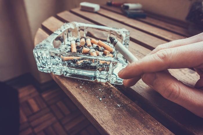 A person ashing a cigarette into an ashtray