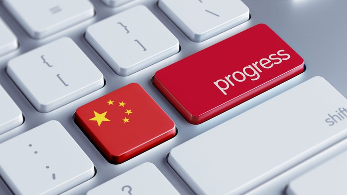 A Chinese flag and the word progress on a keyboard