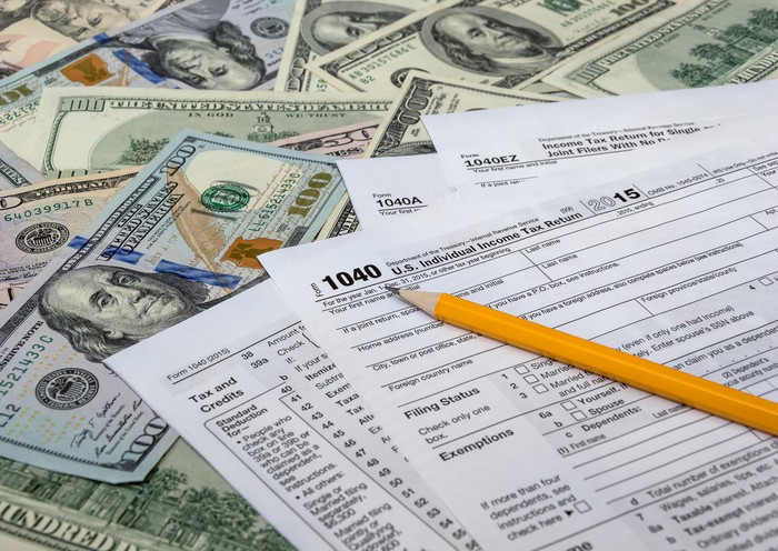 Tax forms with a pencil on top of a spread-out pile of money.
