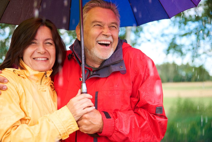Smiling older couple under an umbrella