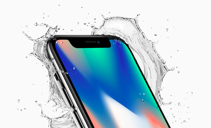 An ad shows the iPhoneX with a bright multicolored wallpaper on the screen is seen with splashing water around it against a white background