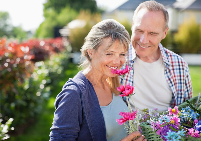 Senior woman smelling flowers and smiling while standing next to a smiling senior man.