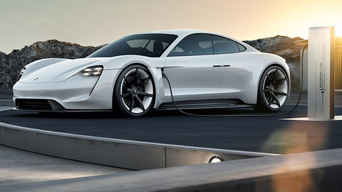 The Porsche Mission E Concept, a white four-door car with a curved sports-car roofline, at a recharging station.