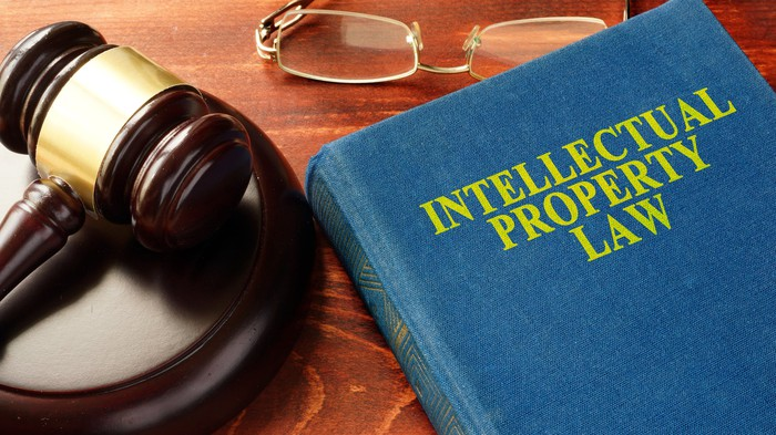 Reading glasses and a judge's gavel resting next to a book titled Intellectual Property Law.