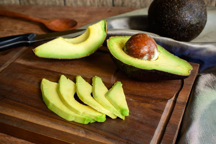 Ripe sliced avocado on wooden chopping board.