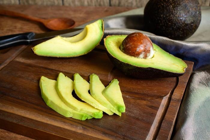 Ripe sliced avocado on wooden chopping board.