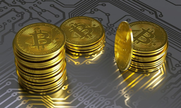 Three piles of gold-colored coins with the bitcoin symbol on top of a representation of a circuitboard.