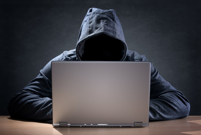 Faceless figure in hoodie facing a laptop.