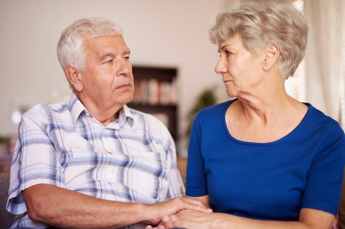 Senior man and woman holding hands and looking at each other with serious expressions