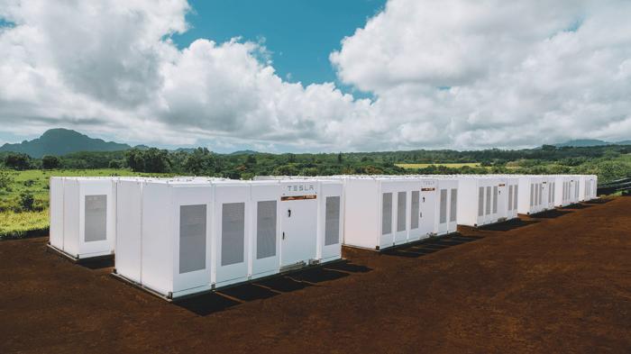 A group of Tesla Powerpacks outside in a field.