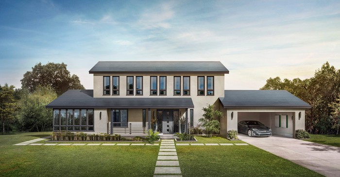 A house with Tesla Smooth Glass solar tiles on the roof and a Model S with two Powerwalls in the garage.