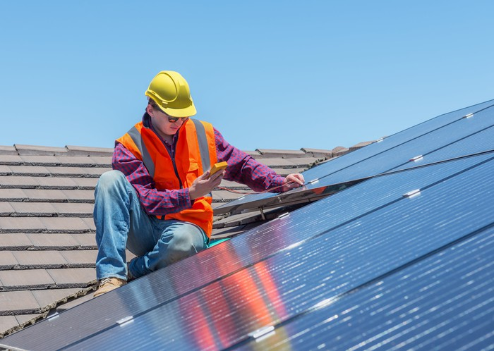 Worker inspecting a rooftop solar installation.