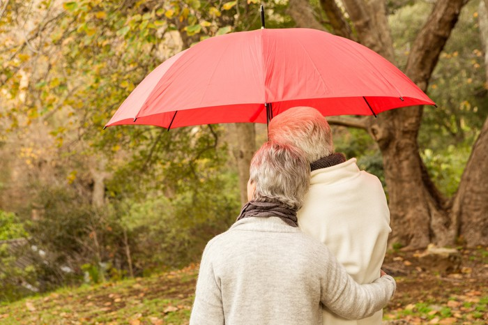 Senior couple outdoors under an umbrella