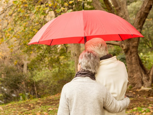 senior couple outdoors under an umbrella_GettyImages-664458886