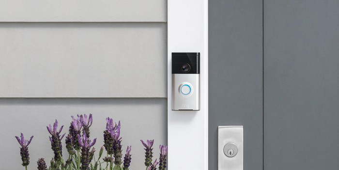 Ring Video Doorbell pictures attacked to the door frame of the front door of a grey house with purple flowers below it
