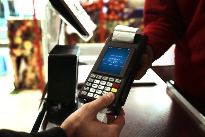 Point-of-sale handheld device being used in an outdoor market.