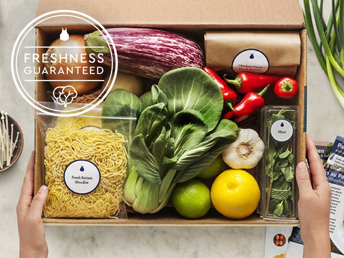 Box of food with vegetables, pasta, herbs, and packaged meat.