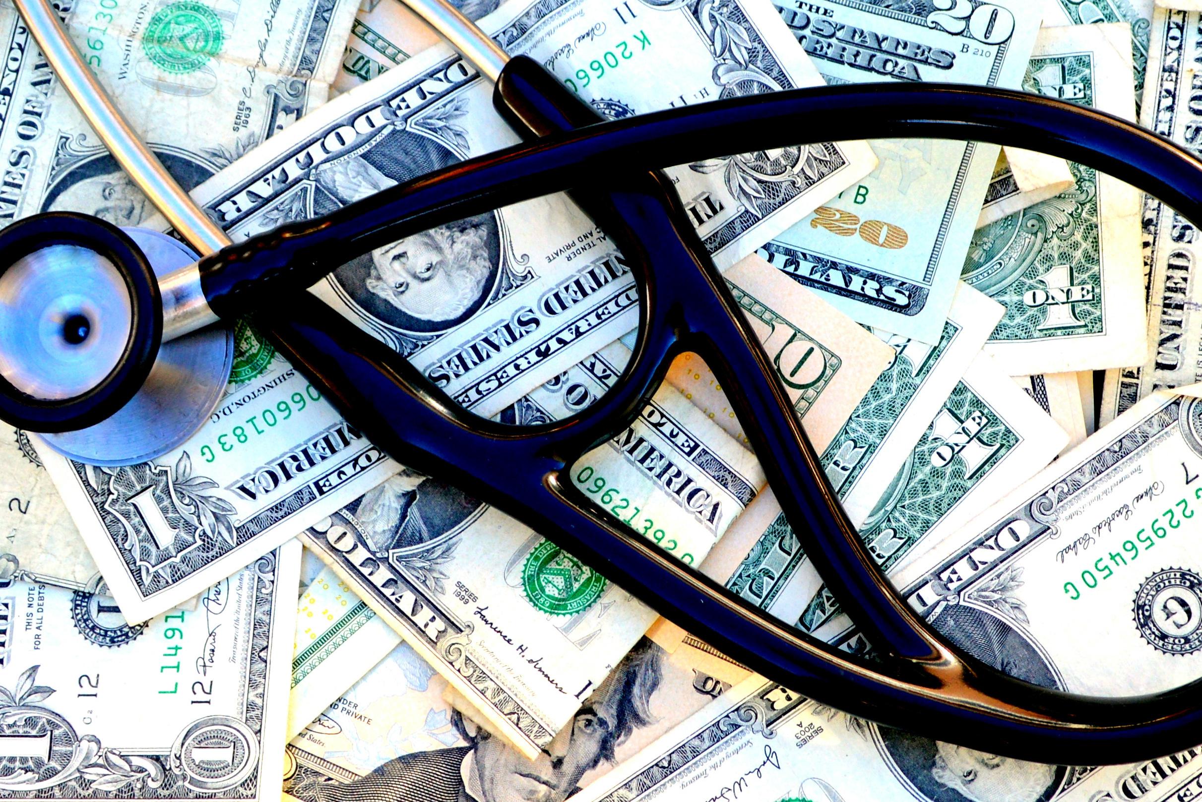 Dark blue stethoscope on top of dollar bills