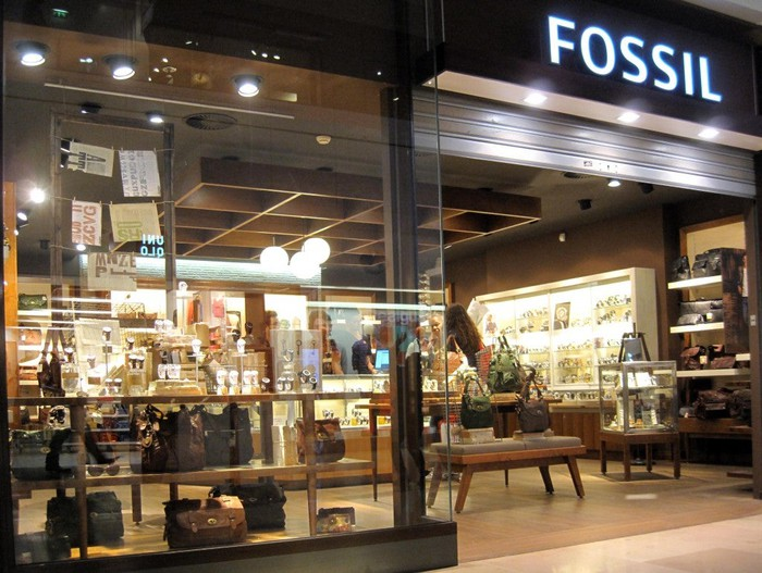 Fossil store location as viewed from outside, with lighted displays and various items in showcases.