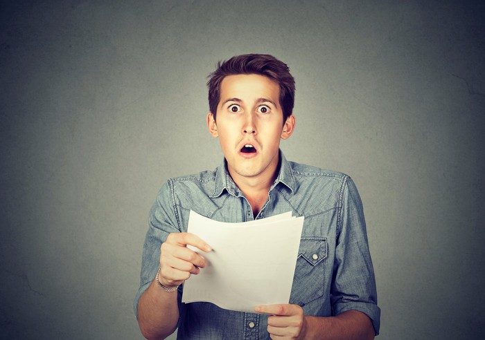 Man looking at a document with a shocked expression on his face