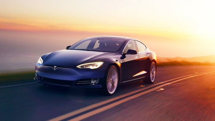 A dark-colored Tesla Model 3 driving on a two-lane street alongside a body of water with the sun shining in the background.