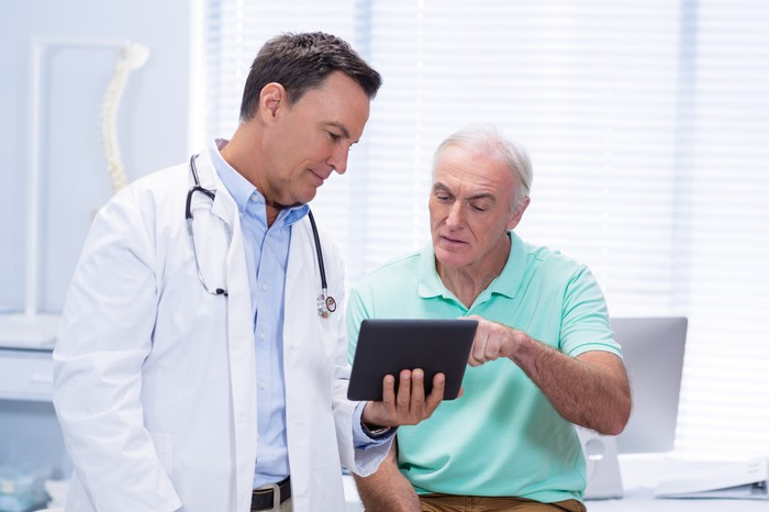 Doctor with patient reading a tablet.