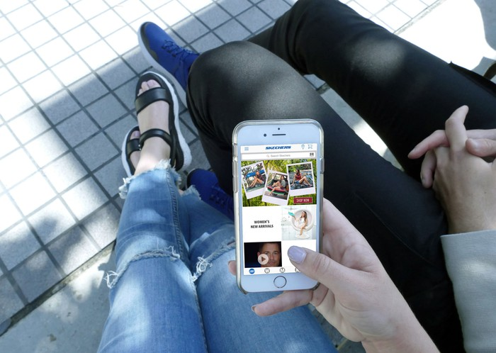 A woman browses the Skechers app with friend while sitting outside.