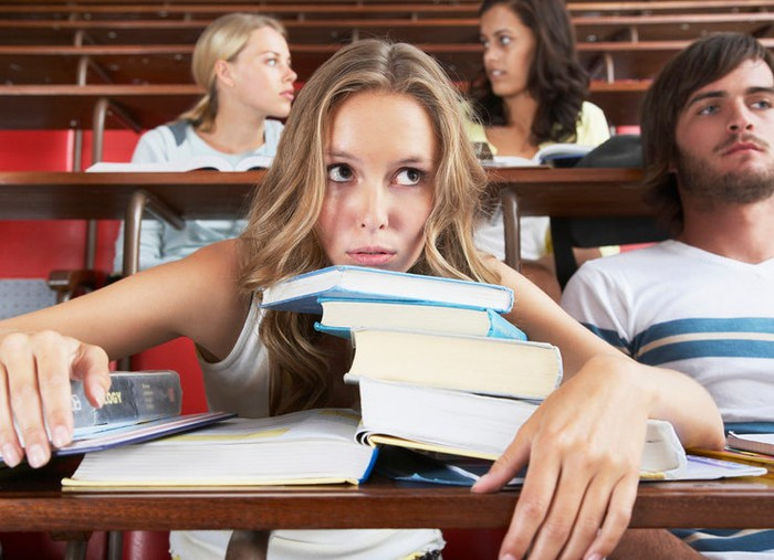 College student in lecture hall with chin on stack of textbooks, looking overwhelmed.