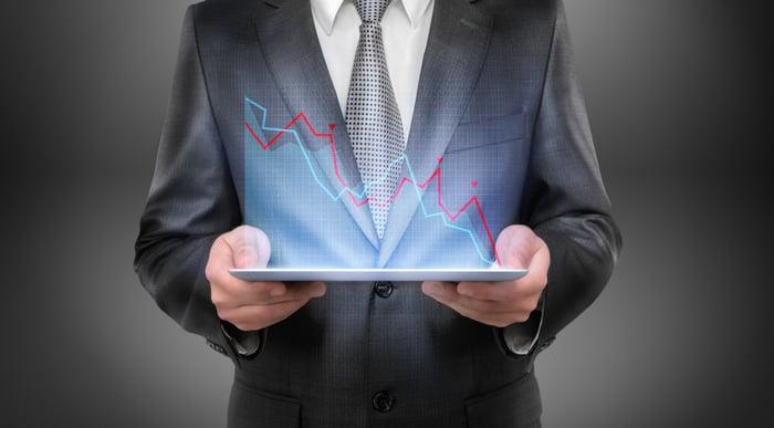 businessman holding tablet projecting downward trending line graphs