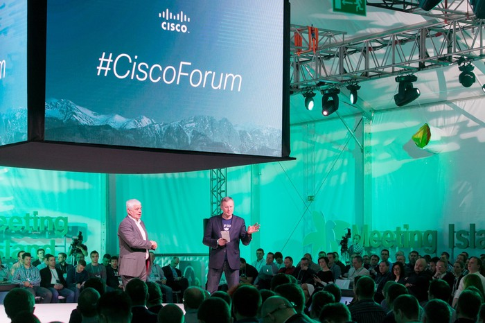 Two people in suits in front of an audience with a screen saying Cisco Forum above them.