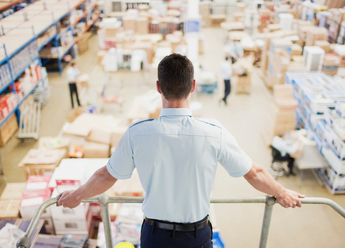 A shipping manager looks out over a delivery floor.