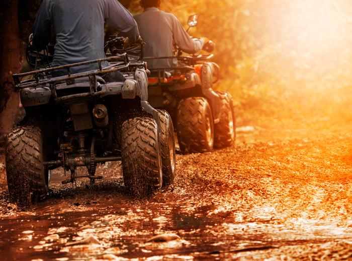 Two people riding ATVs through the mud.