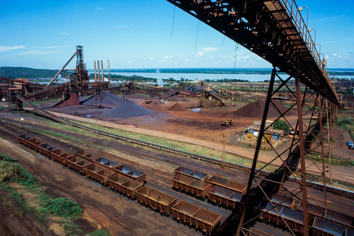 Iron ore mining facility next to a body of water in daylight