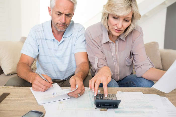 Mature couple sitting on a couch doing paperwork on a table and using a calculator.