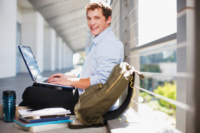 Smiling young man typing on laptop with backpack and pile of books next to him.