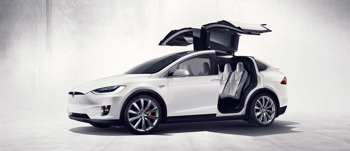 White Tesla Model X vehicle with rear doors open.