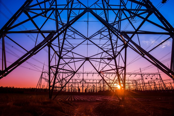 An electricity transmission pylon under twilight skies of blue, purple, and orange with the sun setting in the distance