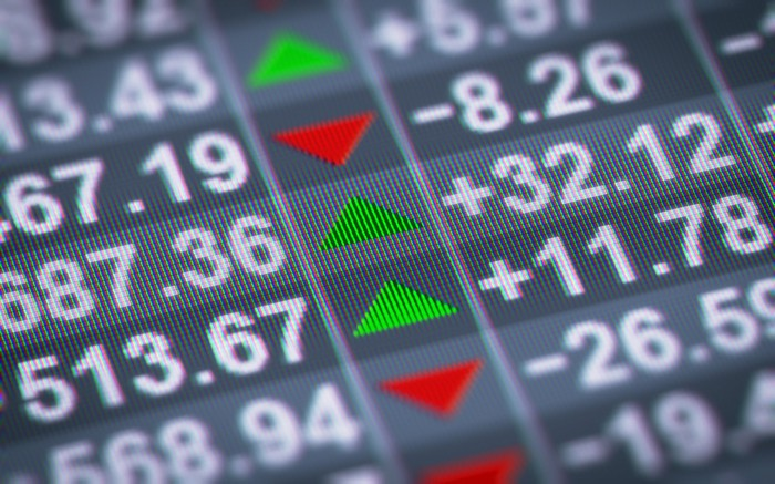 Stock market prices on a digital display with green and red arrows indicating direction.