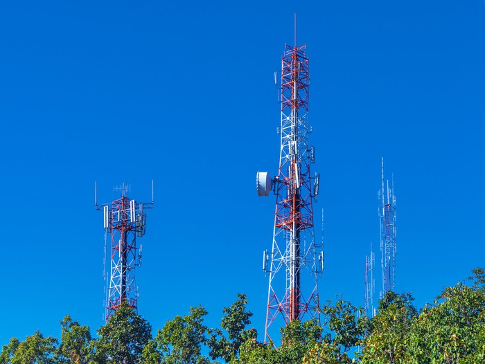 Three cellphone towers standing above treetops.