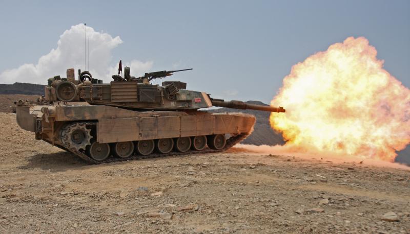 An Abrams tank firing a round atop a hill.