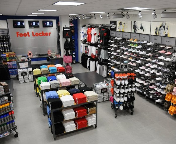 The interior of a Foot Locker store. Shoes are on the shelves, and apparel is on display in the center of the store.